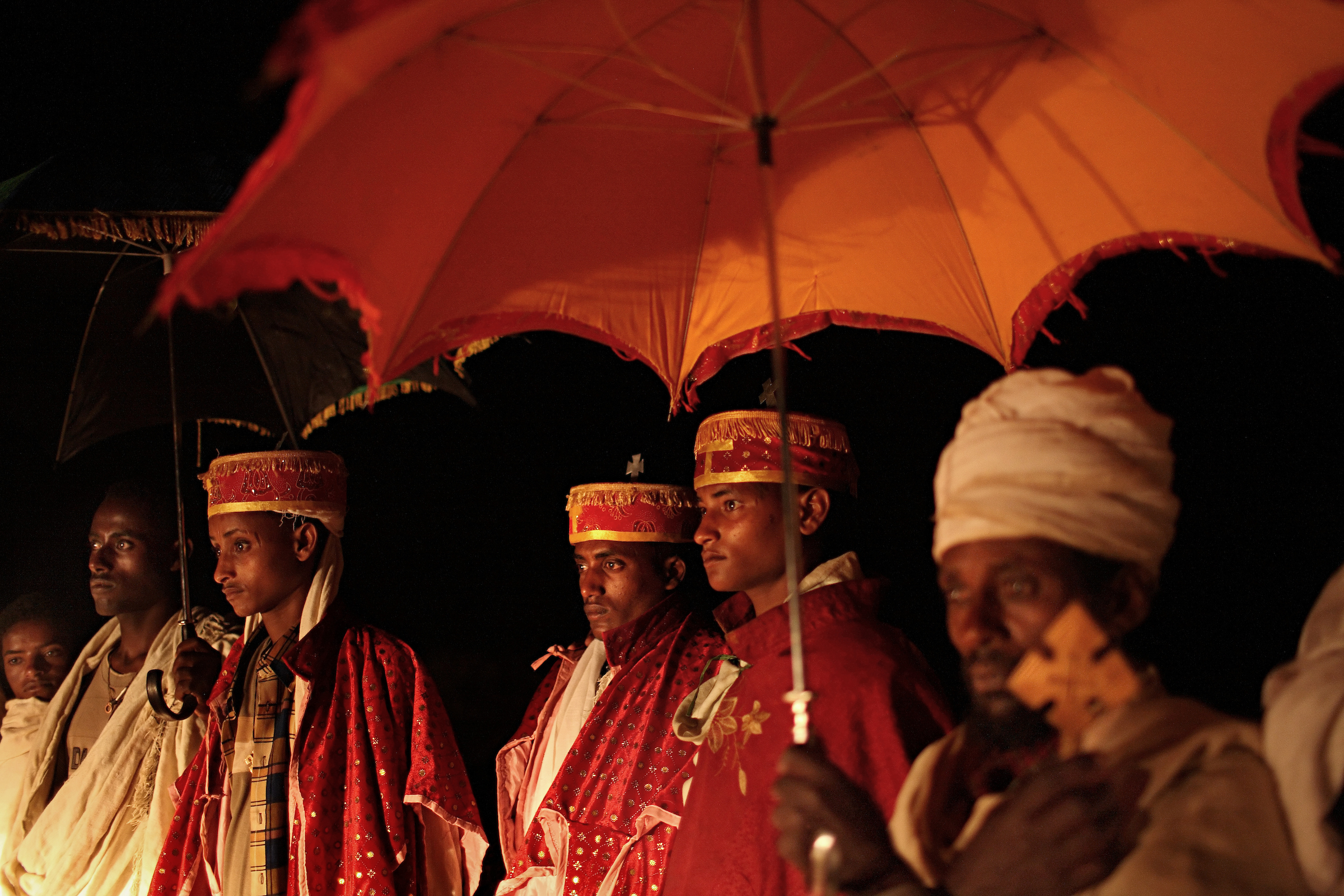 Dressed in traditional Ethiopian Orthodox robes, the wedding party of made up of local priests,including Addisu, 23, walk through the night to pick up his new bride Destaye, 11.