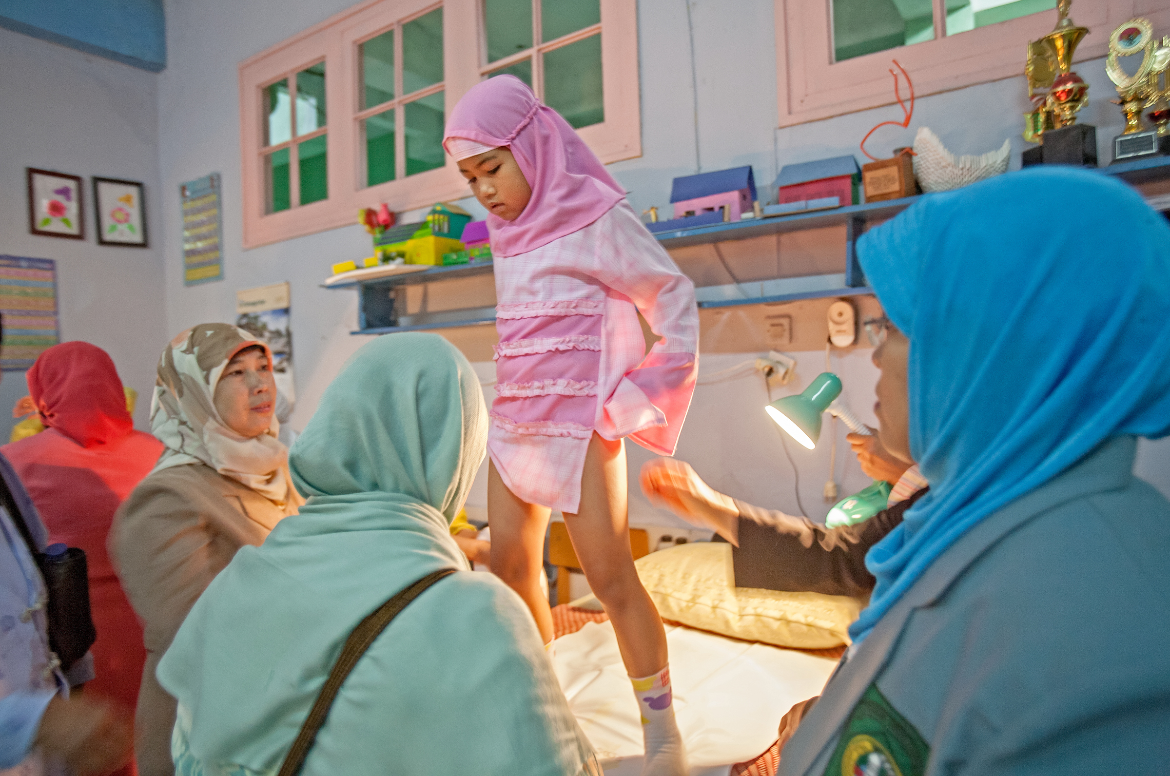 A young girl hesitates as she is prepared to be cut in Bandung, Indonesia, where each spring, parents bring their girls to an emptied-out school for a mass circumcision.