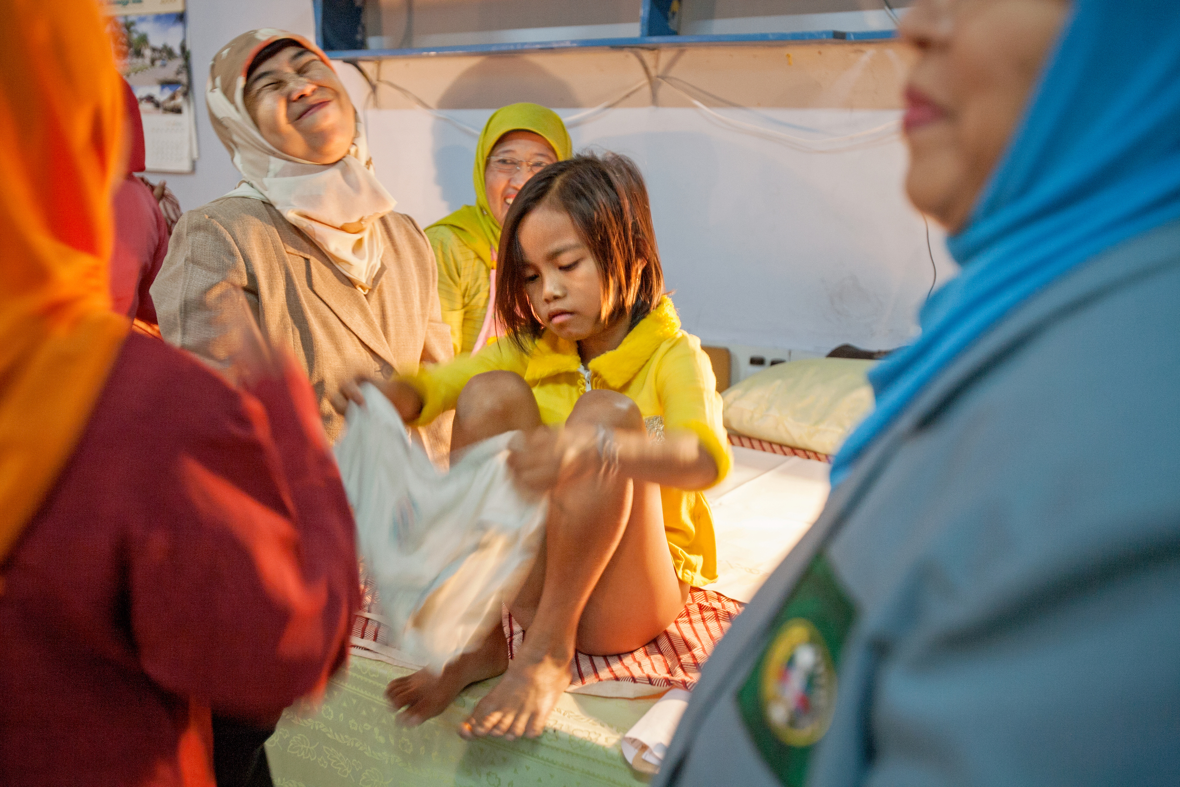 Surrounded by her circumcisers, a young girl is helped back into her underwear after the procedure in Bandung, Indonesia.
