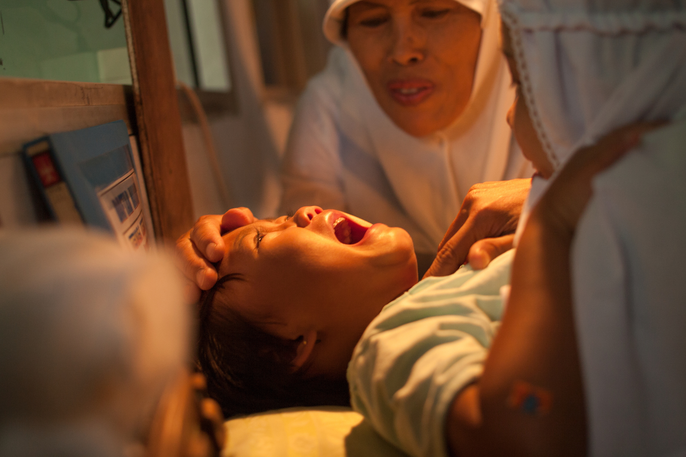 A young girl cries while being circumcised in Bandung, Indonesia.