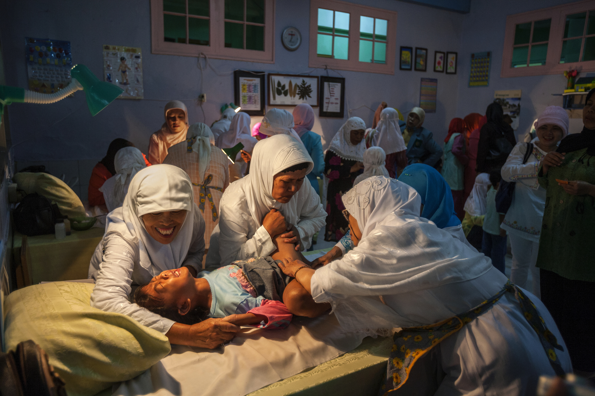 A young girl screams while being circumcised in Bandung, Indonesia.